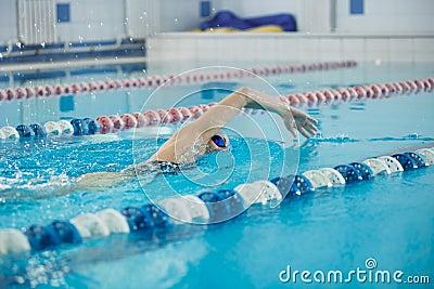Het jonge meisje in beschermende brillen die voorzijde zwemmen kruipt slagstijl