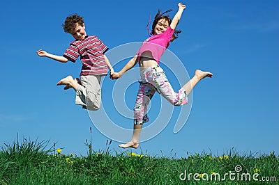 Het jonge meisje en jongens springen