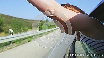 Het jonge meisje heft handen, schreeuw uit open venster van het drijven van auto op wind Glimlach traveling Reis stock footage