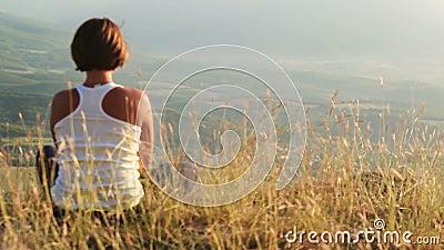 Het jonge meisje ontmoet zon op de bovenkant van heuvel stock video
