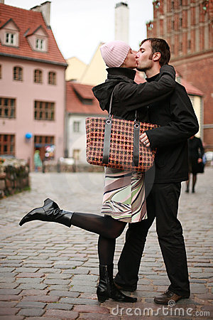 Het jonge paar kussen in stad