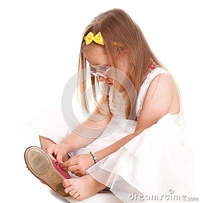 Het kindmeisje probeert om op haar schoenen te zetten isolat
