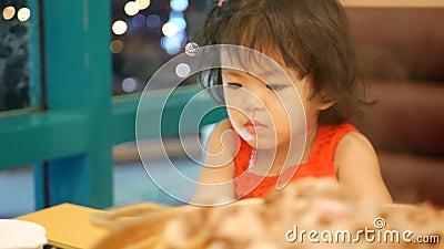 Het kleine Aziatische meisje, 2 jaar oud, die geen aandacht besteedde aan de maaltijd, die eetlust verloor, omdat ze verslaafd wa stock footage