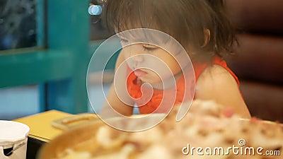 Het kleine Aziatische meisje, 2 jaar oud, die geen aandacht besteedde aan de maaltijd, die eetlust verloor, omdat ze verslaafd wa stock video