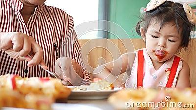 Het kleine Aziatische meisje, 2 jaar oud, leert haar eigen rommel op een eettafel te reinigen tijdens de pizza-maaltijd stock video