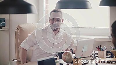 Het knappe jonge CEO zakenman spreken, die bij bureauvergadering lachen Zekere gelukkige werkgever bij zijn werkplaats langzame m stock video