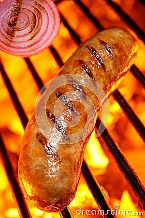 Het koken van een worsthotdog bij de barbecuegrill
