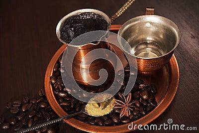 Het koper voor het maken van Turkse koffie met kruidenkoffie die is wordt geplaatst klaar om worden gediend