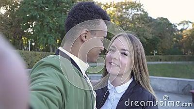 Het kussen van spruiten de tussen verschillende rassen van het tienerpaar zelf op camera stock footage