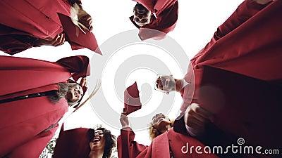 Het langzame schot van de motie lage hoek van gediplomeerden die zich in cirkel bevinden die baretten in de hemel en het lachen w stock footage