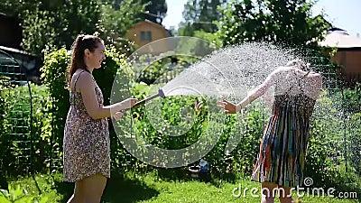 Het leuke meisje giet haar meisjewater van tuinslang op groen gazon op een hete de zomer zonnige dag Blonde en brunette in kledin stock videobeelden