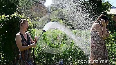 Het leuke meisje giet haar meisjewater van tuinslang op groen gazon op een hete de zomer zonnige dag Blonde en brunette in kledin stock footage