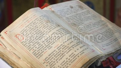 Het lezen van het Heilige Evangelie Draait de handen Orthodoxe priester de pagina stock footage