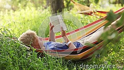 Het lezen van laatste best-seller in comfortabele Hangmat in de schaduwen van appelbomen stock videobeelden