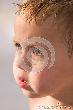Het Loensen van de Jongen van de close-up Ogen in Zon