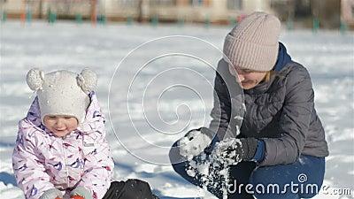 Het mamma en de dochter hebben pret op de straat in een mooie de winter sneeuwdag, werpt mijn moeder sneeuw bij het meisje, het m stock footage