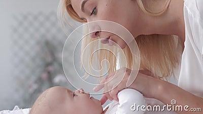 Het mamma kust kleine handen haar aanbiddelijk babymeisje dat op veranderende lijst dicht omhoog ligt stock footage
