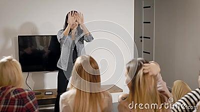 Het meisje bevindt zich voor haar vriend in huis en het dansen, tonend scènes voor het veronderstellen, charadesspel stock video