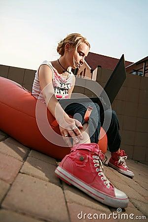 Het meisje dat van de blonde laptop bekijkt