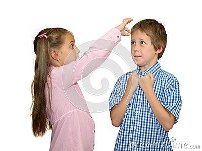 Het meisje geeft flick op het voorhoofd van de jongen, op wit
