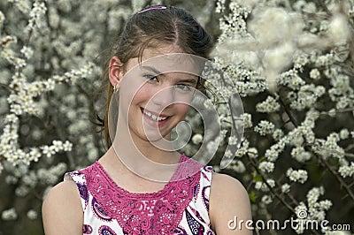 Het meisje met witte bloemen kijkt schuw