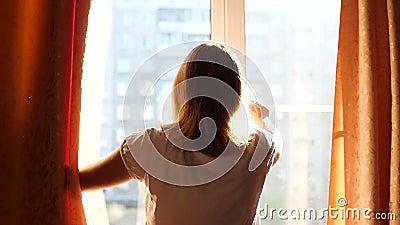 Het meisje opent de gordijnen op een Zonnige dag