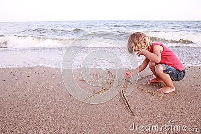 Het meisje trekt een zon in het zand op het strand