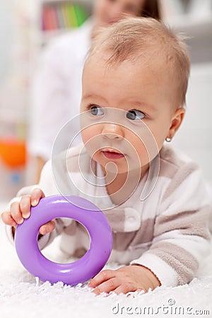 Het meisje van de baby met plastic stuk speelgoed