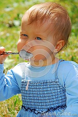 Het meisje van de baby openlucht eten zelf