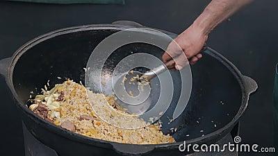 Het mengen van kokend pilau met vlees in grote kazan in open plek stock video
