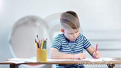 Het middel schoot zeker weinig beeld van de jongenstekening op papier gebruikend kleurpotloden zittend op lijst stock video