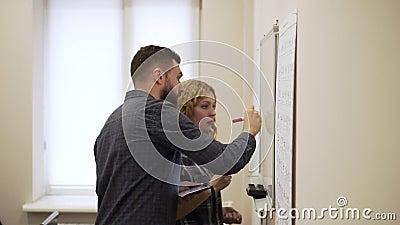 Het middelgrote schot van de Jonge mens en de vrouw trekken een grafiek op witte raad in bureau stock footage