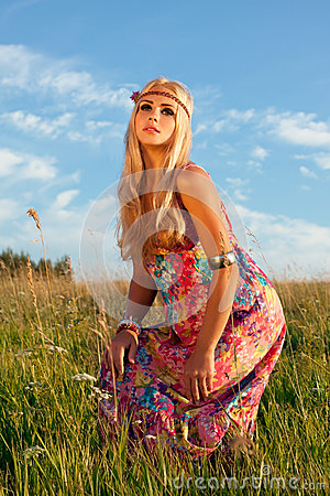 Het mooie blonde stellen in weide tegen blauwe hemel