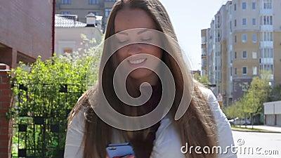 Het mooie jonge meisje schrijft een bericht om een smartphone te gebruiken lopend onderaan de straat in de zomer en het glimlache stock videobeelden