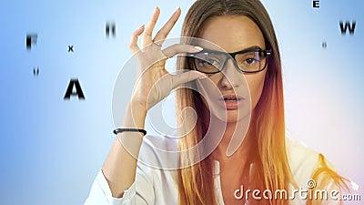 Het mooie meisje controleert visie in een oftalmoloog met glazen stock videobeelden