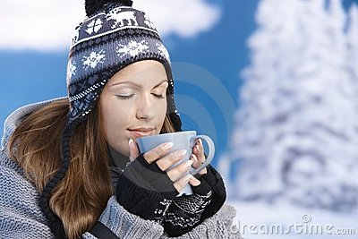 Het mooie meisje dat hete thee in de winterogen drinkt sloot