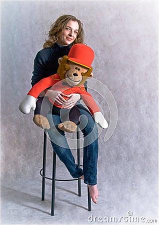 Het mooie meisje houdt een stuk speelgoed aap in handen.