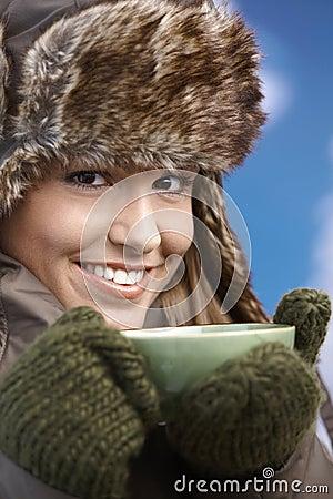 Het mooie meisje kleedde omhoog het warme het drinken thee glimlachen