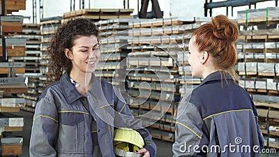 Het mooie vrouwelijke fabrieksarbeider hoge fiving met haar collega stock video