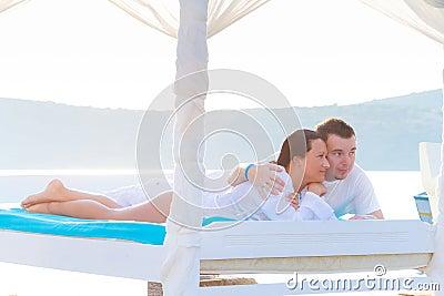 Het ontspannen op luxe wit bed bij het overzees