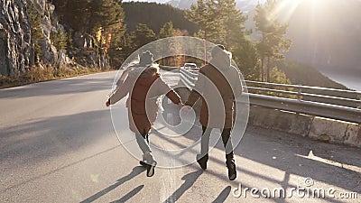 Het paar kijkt uit naar het avontuur Samen lopen ze langs een asfaltweg of een snelweg in de winter tussen stock videobeelden