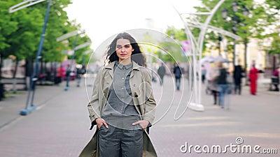 Het portret die van de tijdtijdspanne van jong brunette zich in de straat alleen onder menigte bevinden stock videobeelden
