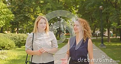 Het portret van de sluiting van twee vrouwelijke vrienden die wandelen terwijl ze vrolijk lachen in het park in de openlucht stock videobeelden