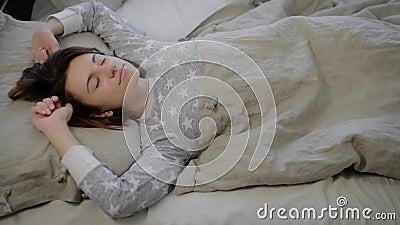 Het portret van jonge donkerbruine vrouw kleedde zich in grijze pyjama die die en in bed liggen slapen met linnen thuis wordt beh stock videobeelden