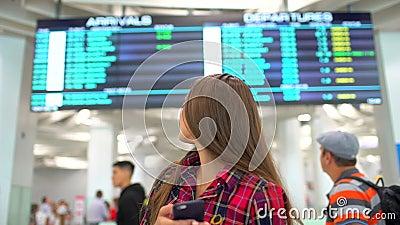 Het portret van jonge glimlachende vrouw die smartphone voor het controleren van haar vlucht op de aankomst met behulp van dient  stock videobeelden