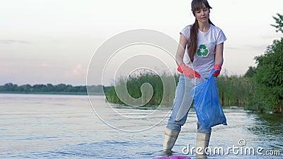 Het probleem van plastic verontreiniging, jonge vrijwilligersvrouw in rubberlaarzen maakt strand van afval schoon en verzamelt po stock video
