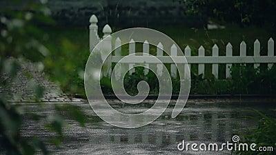 Het regenweer in de voorsteden, de regendruppels die op de bestrating vallen, de meteorologie en het klimaat stock video