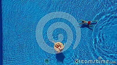 Het satellietbeeld van de mens zwemt in de pool terwijl het meisje op een vlotter van de doughnutpool ligt stock footage