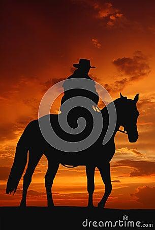 Het silhouet van de cowboy in zonsopgang