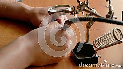 Het sluiten van de handen van de technicus doet wat reparatie of een ambacht op een bureau met vergrootglas en roterend hulpmidde stock video